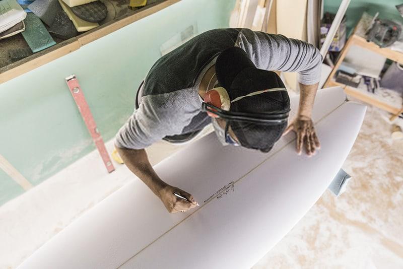shaper signing on surfboard foam