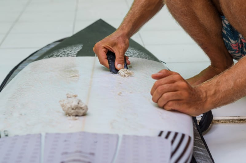 removing old wax from surfboard with a scrapper